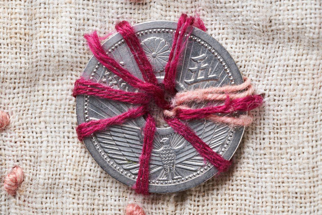 千人針の五銭硬貨 / 5 sen coin sewed on a Sen-nin Bari (bellyband with 1000 stitches)